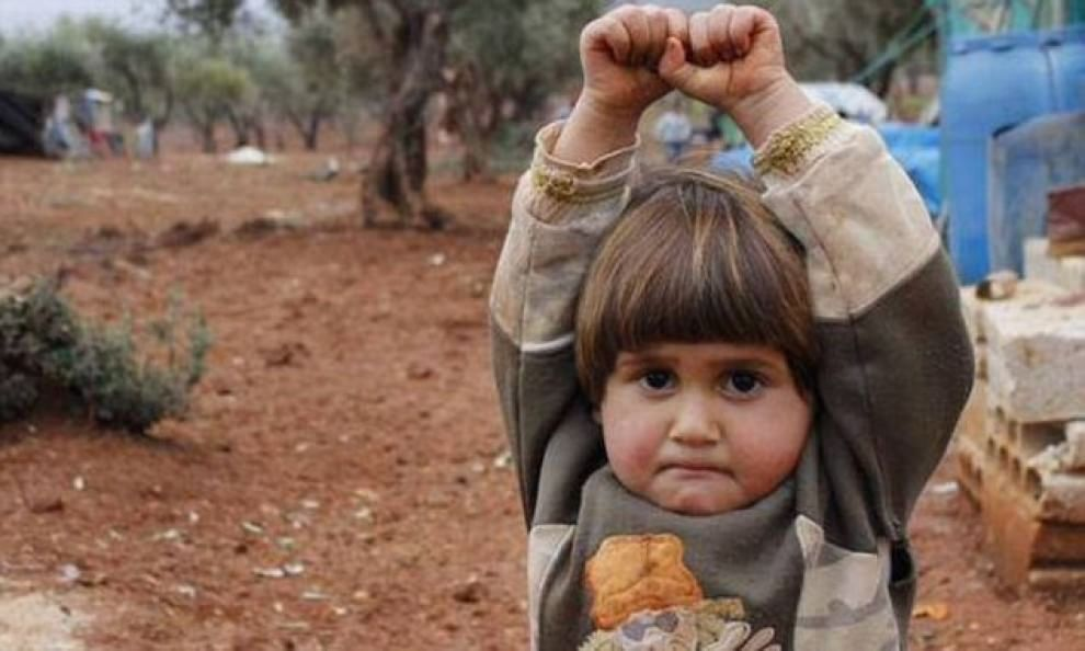 Siria, bimba si arrende alzando le mani davanti alla macchina fotografica