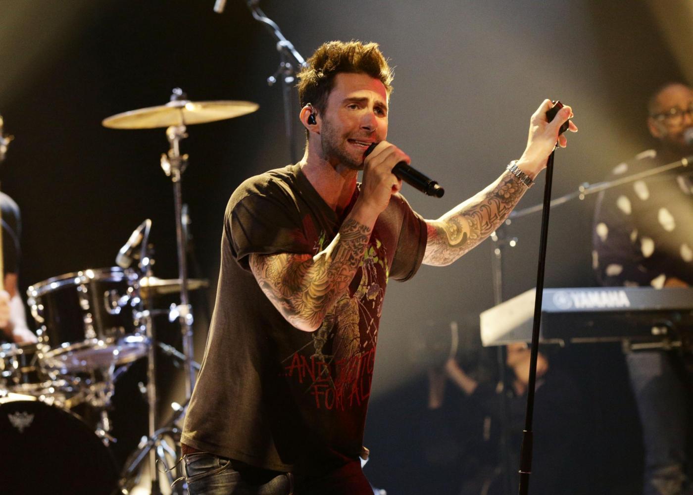 Adam Levine dei Maroon 5 tira un microfono ad una fan e poi la fa salire sul palco