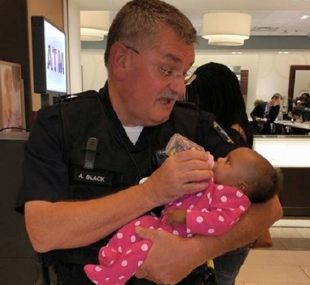 La foto virale del poliziotto che allatta una bimba mentre la madre ha un attacco epilettico