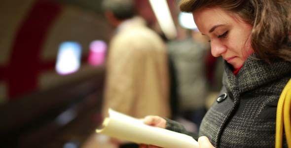 Ragazza che legge un libro in metro