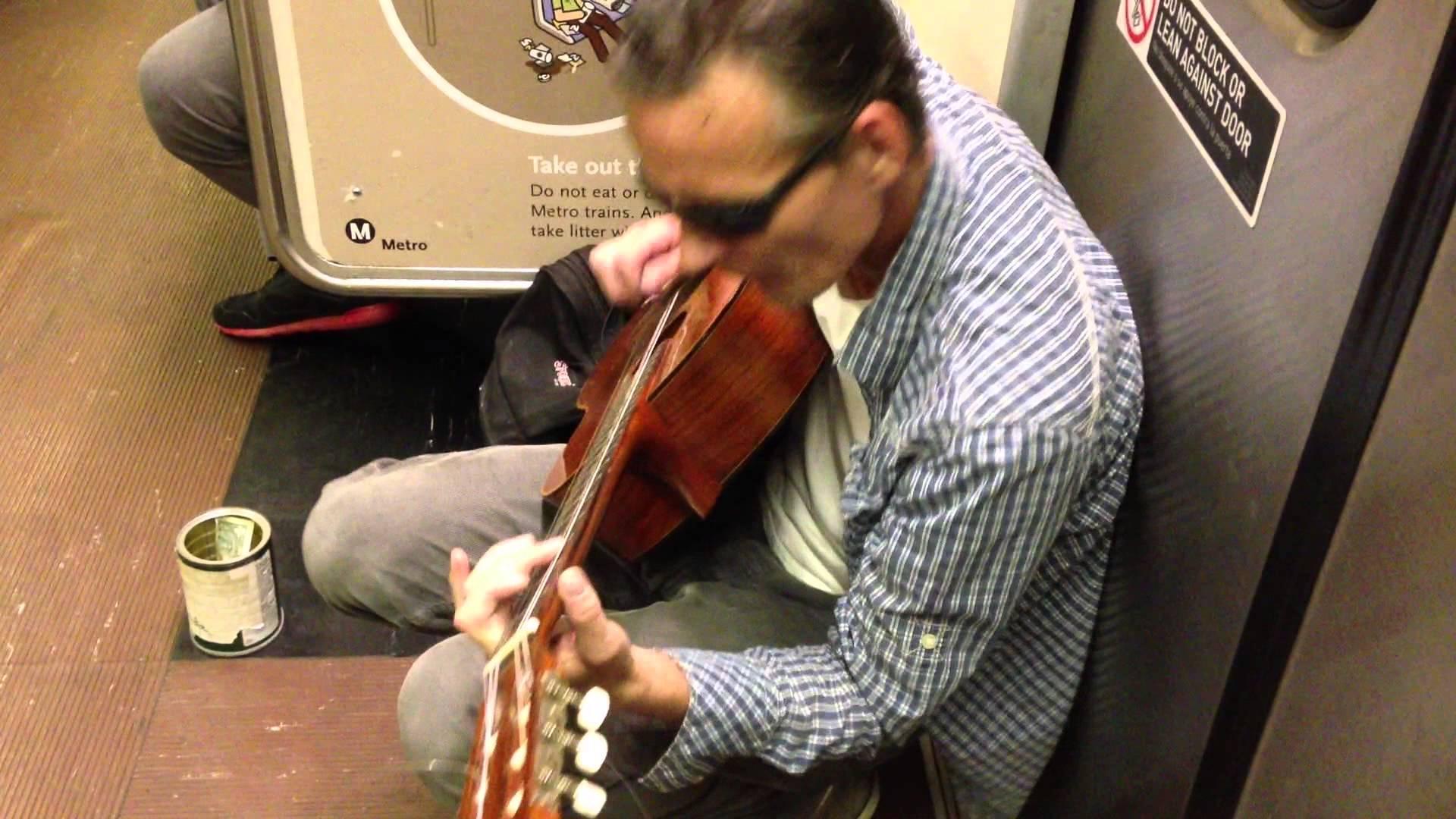 Uomo che suona chitarra in metro