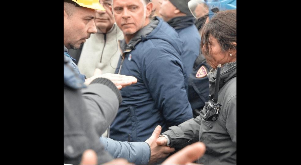 Poliziotta toglie il casco e stringe la mano al lavoratore dellIlva