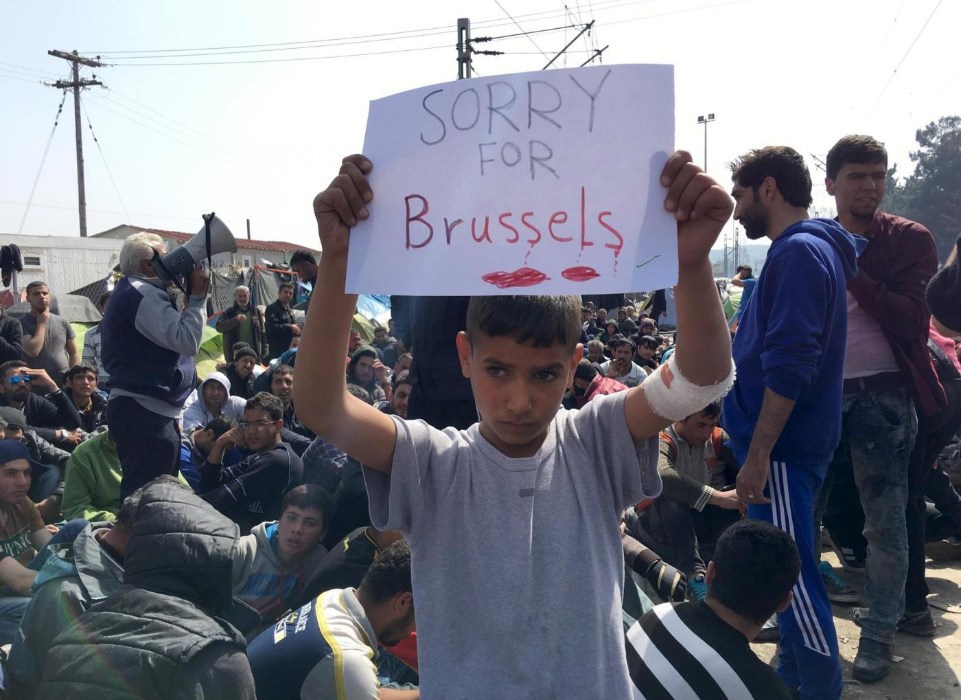 Idomeni, bambino profugo alza cartello di scuse per attentati Bruxelles