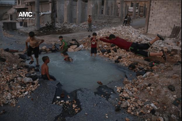 Aleppo, i bambini trasformano il cratere di una bomba in piscina