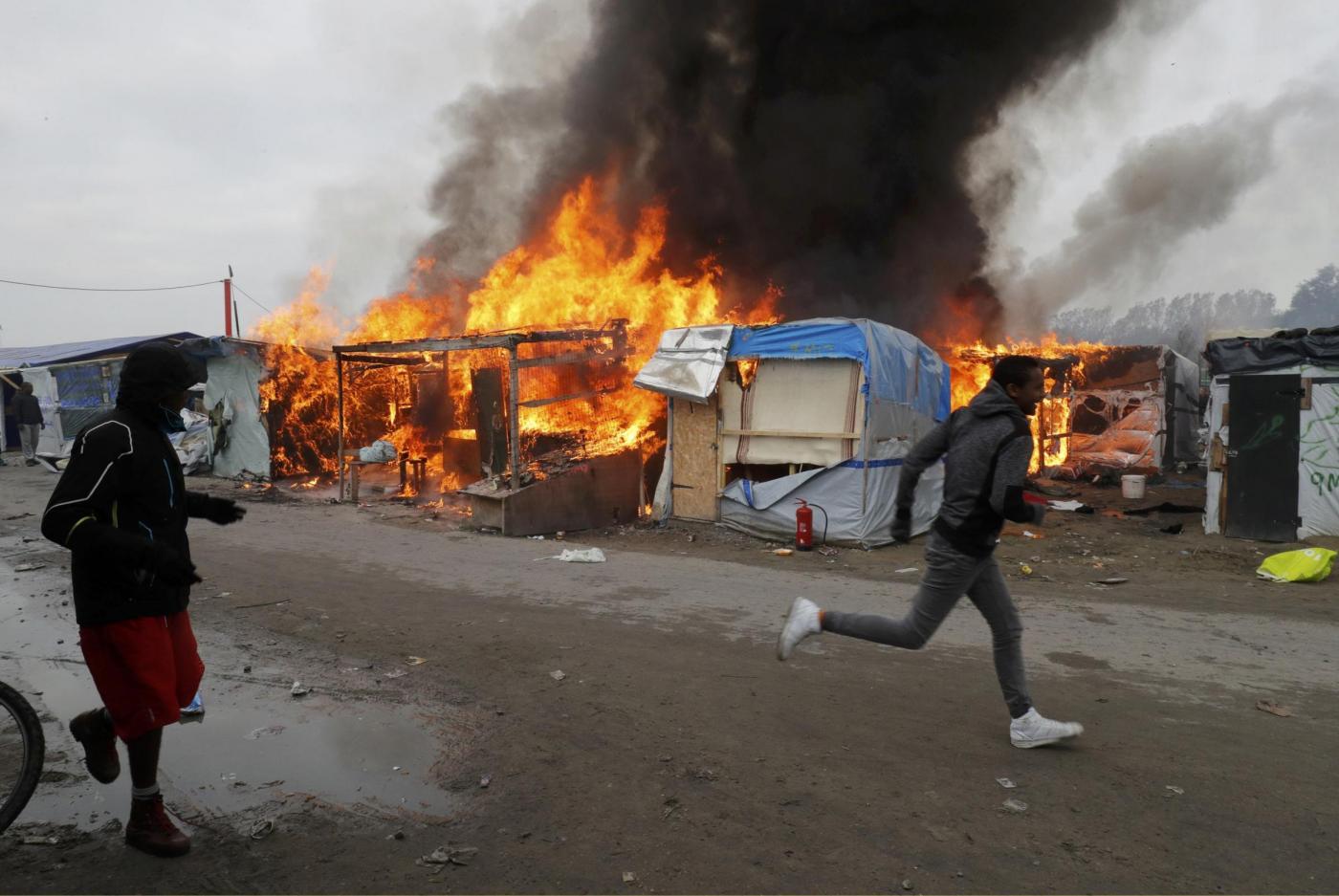 Calais, migranti danno fuoco alle loro baracche prima di lasciare La Giungla