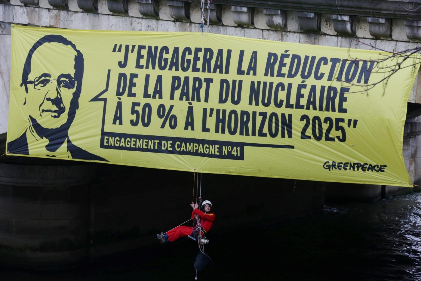 Attivisti Greenpeace appendono striscione contro Hollande sotto il ponte Concorde a Parigi.