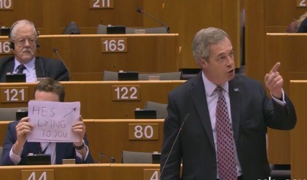 Farage a Bruxelles, dietro di lui spunta un cartello: 'Vi sta mentendo'