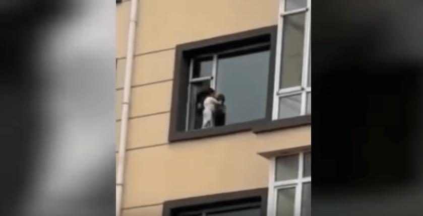 Bimbo gioca camminando sul davanzale della finestra al quinto piano