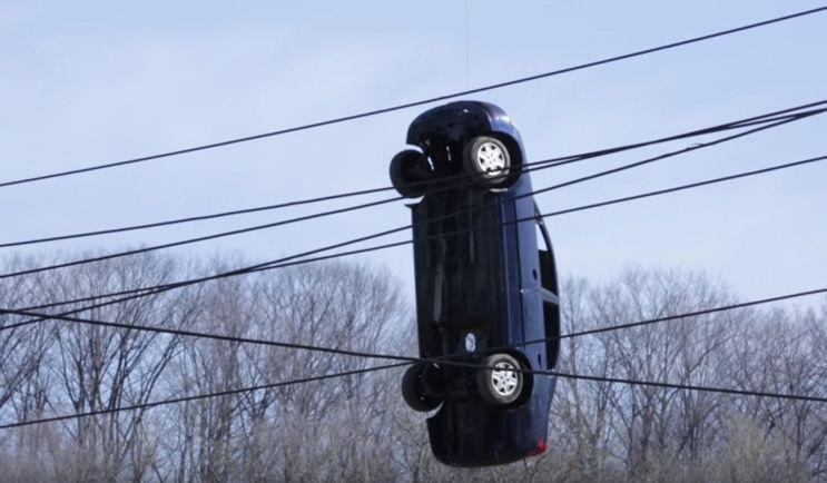 Auto penzola misteriosamente tra i cavi elettrici: come ci è finita?