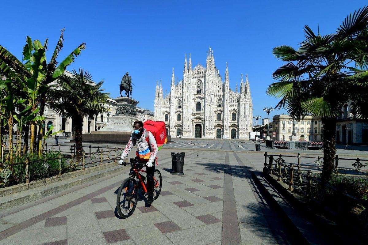 Un rider di Just Eat davanti al Duomo di Milano durante il lockdown