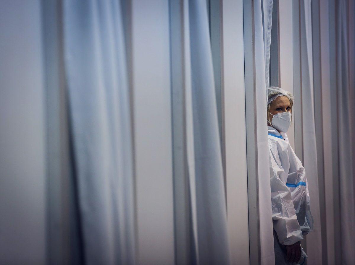 Covid - Un operatore sanitario attende fuori da uno stand di vaccinazione nel centro espositivo della Fiera di Belgrado a Belgrado, in Serbia, martedì 19 gennaio 2021. Lunedì, il direttore generale dell'Orgnizzazione della sanità mondiale Tedros Adhanom Ghebreyesus ha detto che i produttori di farmaci hanno dato la priorità all'approvazione normativa nei ricchi paesi in cui i profitti sono più alti, piuttosto che inviare dossier completi per ottenere il via libera dall'ente sanitario globale
