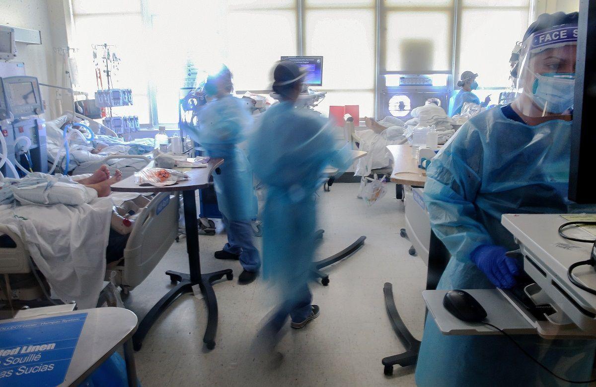 I medici si prendono cura dei pazienti COVID-19 in una ICU (unità di terapia intensiva) improvvisata presso l'Harbour-UCLA Medical Center il 21 gennaio 2021 a Torrance, in California. L'ospedale ha terminato la sua capacità di terapia intensiva a causa del coronavirus ed è stato costretto a trattare più pazienti COVID-19 che richiedono cure a livello di terapia intensiva insieme in stanze convertite progettate per livelli di assistenza inferiori. La California è diventata il primo stato della nazione a registrare 3 milioni di infezioni note da COVID-19. La contea di Los Angeles ha riportato più di 250 morti per COVID-19 il 21 gennaio