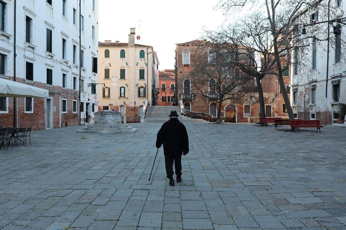 Un uomo anziano cammina da solo in una piazza vuota il 14 febbraio 2021 a Venezia, Italia. Venezia sta segnando un secondo periodo di Carnevale ribaltato dalla pandemia del covid-19, dopo che la celebrazione dello scorso anno è stata interrotta da un blocco imposto all'improvviso, mentre l'Italia lottava per frenare le epidemie del covid-19 che imperversavano nel nord del paese. Quest'anno, il festival è stato nuovamente annullato a causa delle continue restrizioni alle riunioni pubbliche, lasciando le strade e le piazze di Venezia stranamente silenziose in un momento in cui sarebbero state affollate da milioni di turisti