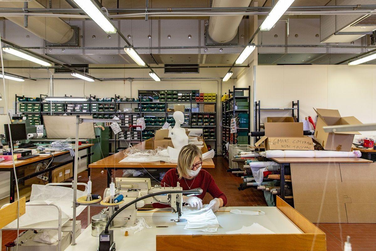 Un dipendente cucisce una maschera protettiva per il viso presso la sede di Miroglio Fashion Srl, che ha cambiato la sua linea di produzione dalla produzione di abbigliamento e accessori femminili alla realizzazione di maschere, ad Alba, in Italia, giovedì 19 marzo 2020