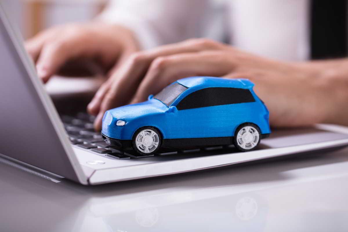 auto blu giocattolo appoggiata su un un pc