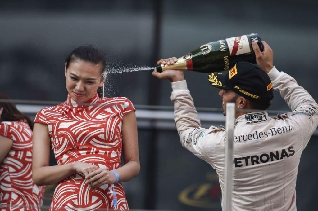 Hamilton spruzza champagne sul viso della hostess, è bufera