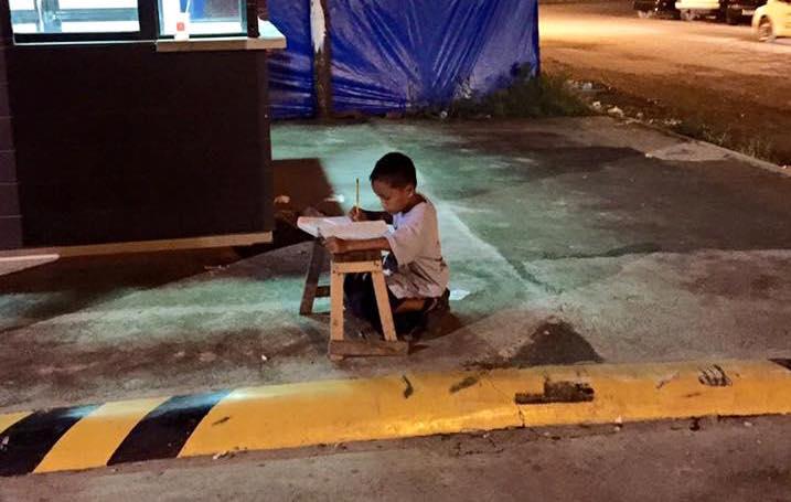 Il bambino filippino che fa i compiti alla luce di un lampione