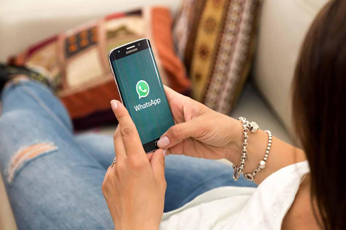 Ragazza che ha in mano un telefono Samsung con sopra installato WhatsApp