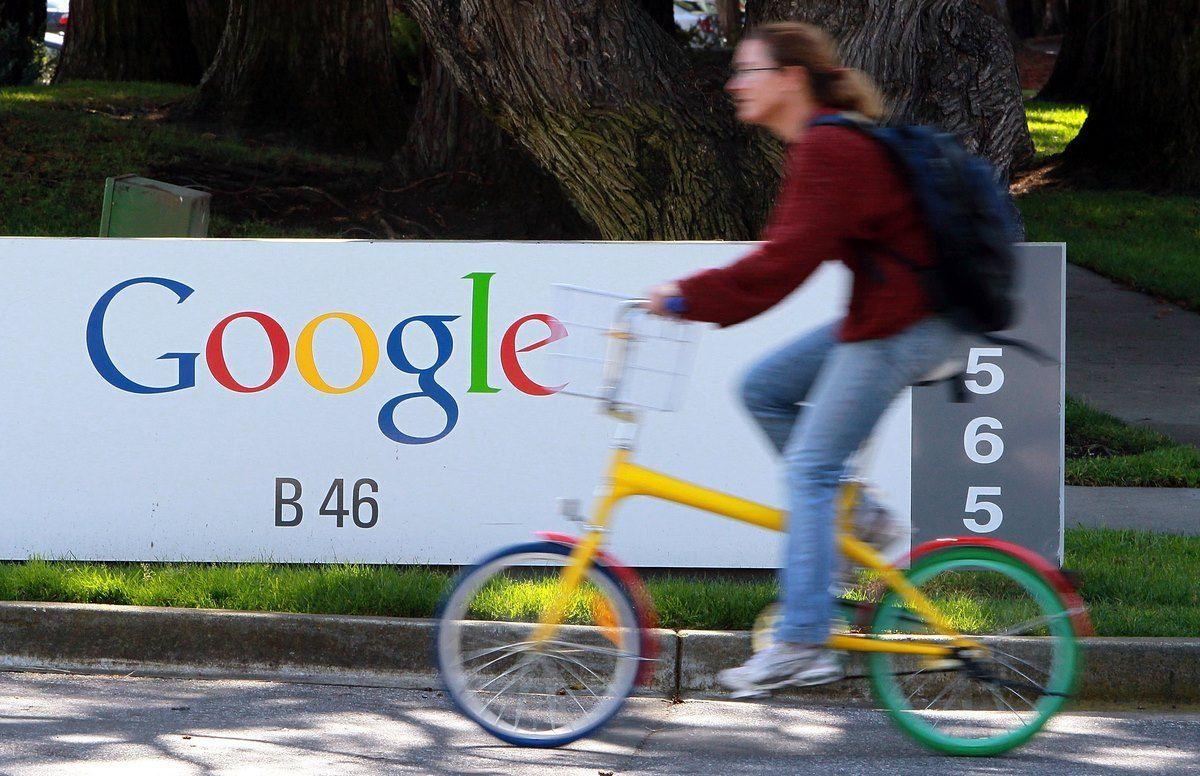 Una donna passa in bicicletta davanti all'insegna di Google