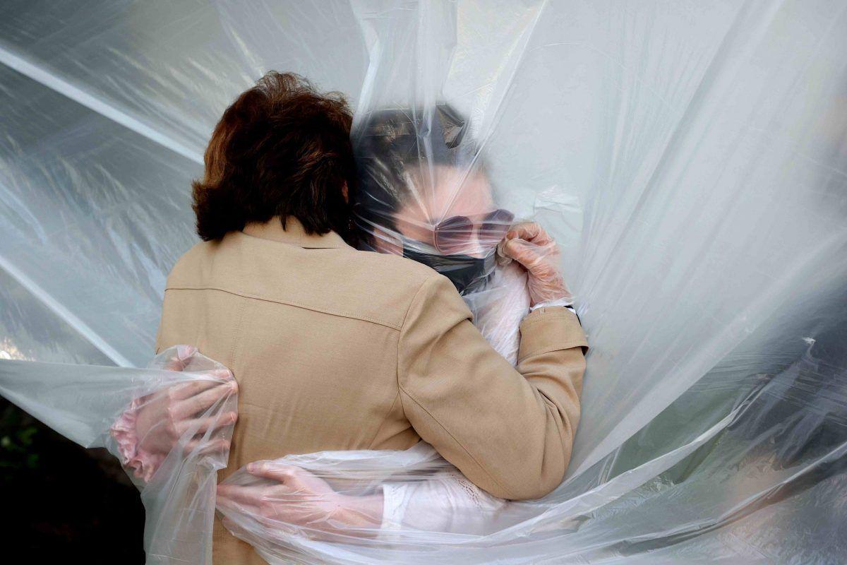 Giornata mondiale degli abbracci Olivia Grant (R) abbraccia sua nonna, Mary Grace Sileo attraverso un panno di plastica appeso su una linea di vestiti fatta in casa durante il weekend del Memorial Day il 24 maggio 2020 a Wantagh, New York. È la prima volta che hanno contatti di qualsiasi tipo da quando il blocco della pandemia del coronavirus COVID-19 è iniziato a fine febbraio.